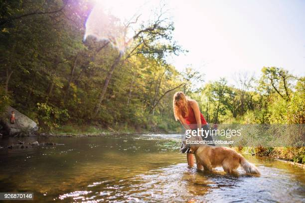 Woman standing in a river with a golden retriever dog