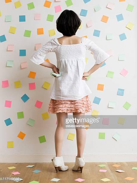Mujer de pie en una habitación de notas adhesivas