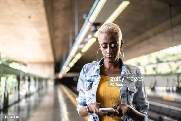 mujer de pie en una plataforma de metro usando teléfono celular - mirar hacia abajo fotografías e imágenes de stock