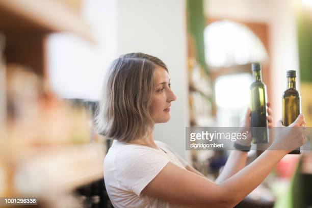 woman standing in a supermarket comparing bottles of olive oil - olive oil stock pictures, royalty-free photos & images
