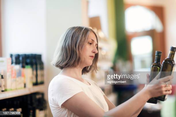 Woman standing in a supermarket comparing bottles of olive oil