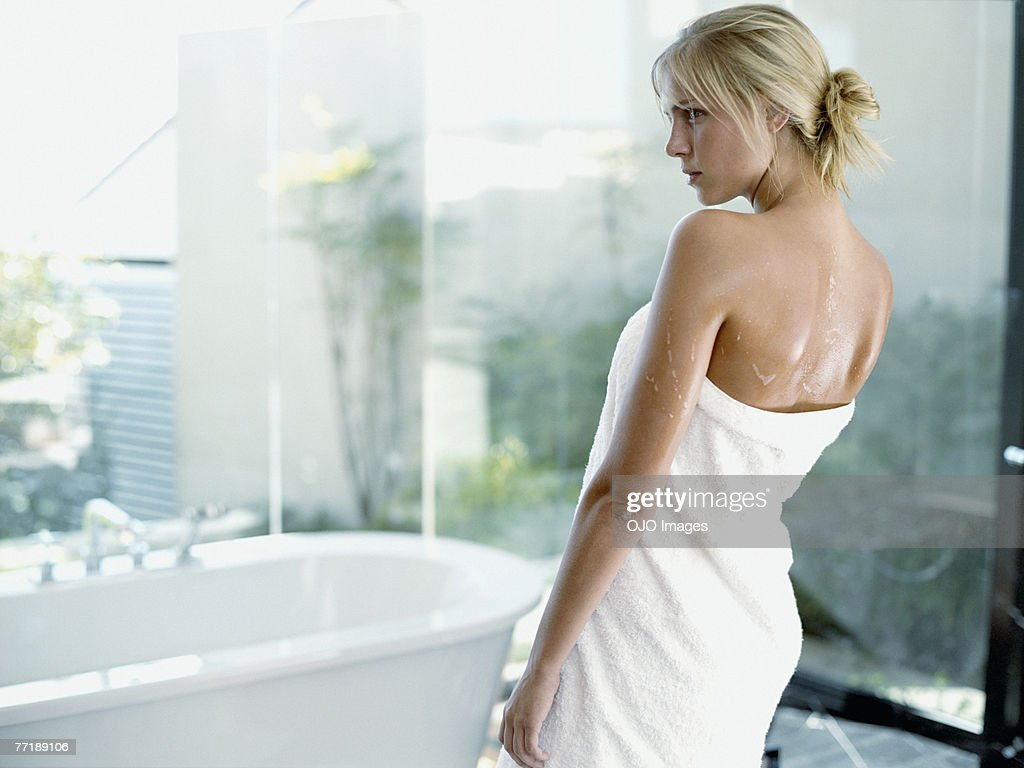 A woman standing in a towel by the bathtub : Stock Photo
