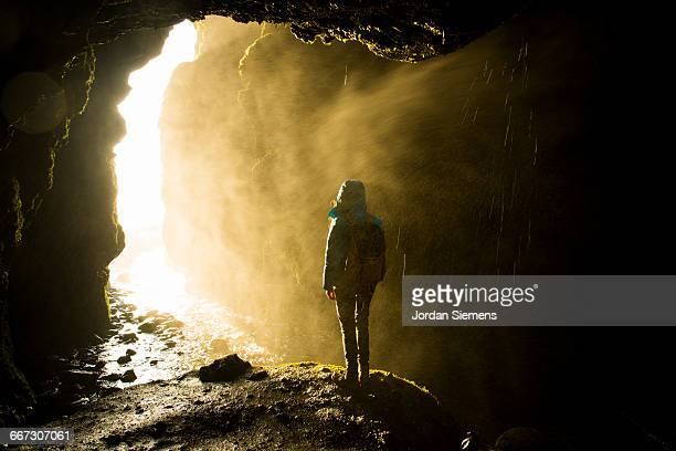 A woman standing in a wet cave.