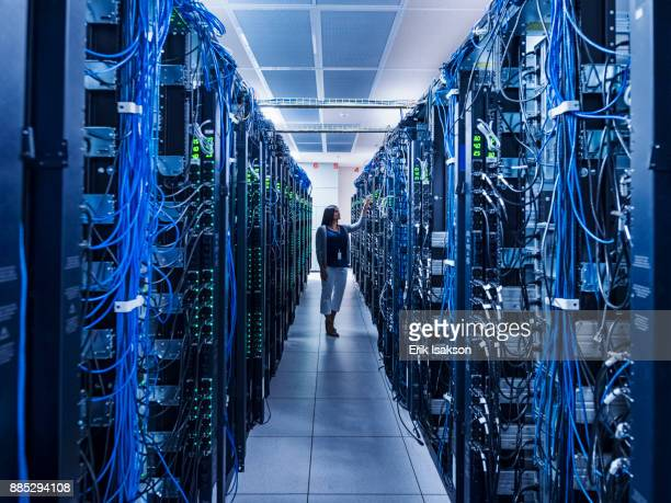 woman standing in aisle of server room - data center stock pictures, royalty-free photos & images