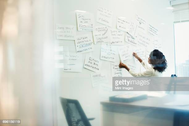 A woman standing in an office arranging pieces of paper pinned on a whiteboard.