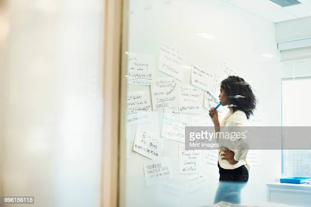 A woman standing in an office looking at pieces of paper pinned on a whiteboard.