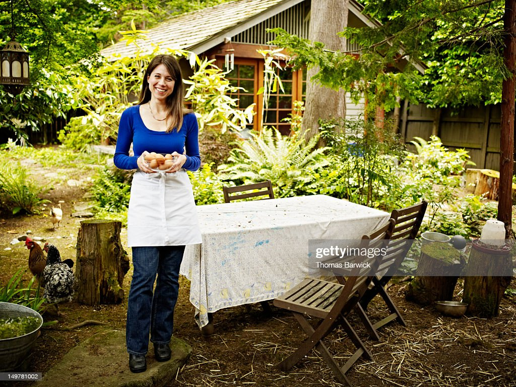 Woman standing in backyard holding bowl of eggs : Stock Photo