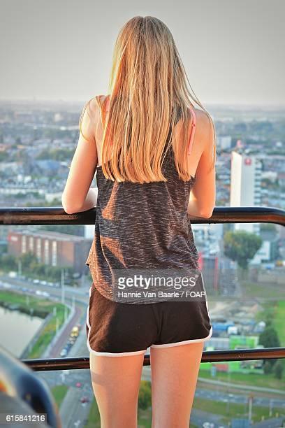 Woman standing in balcony looking at the city