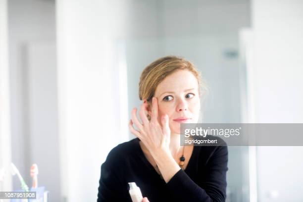 woman standing in bathroom applying make-up - concealer stock pictures, royalty-free photos & images