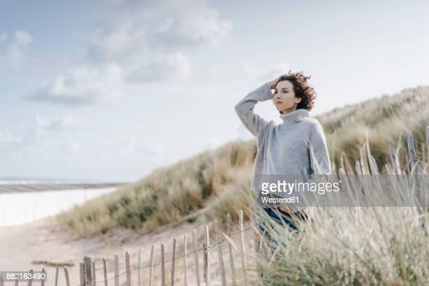 Woman standing in beach dune