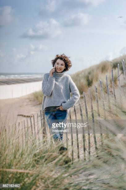 Woman standing in beach dune talking on cell phone