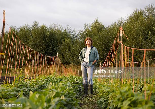 Woman standing in bean field, hands in pockets, portrait