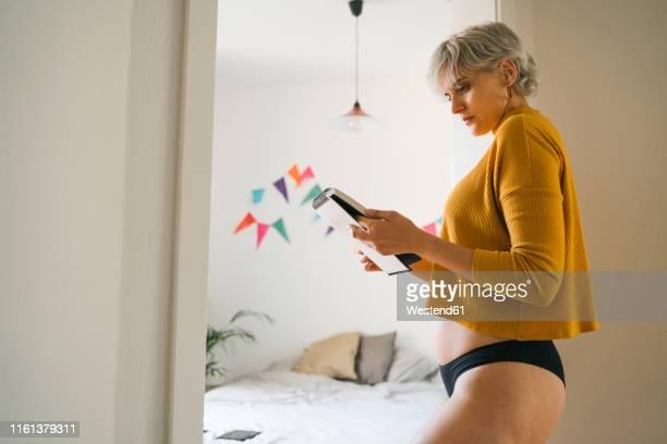 woman standing in bedroom at home holding notepad - frau in slip stock-fotos und bilder