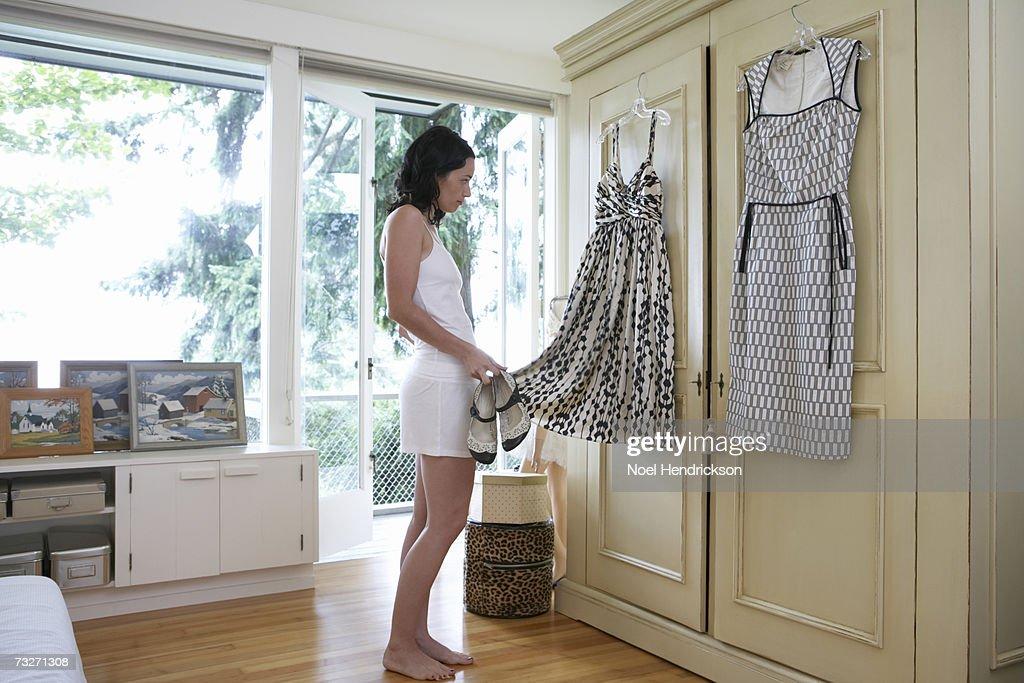 Woman standing in bedroom, choosing dress : Stock Photo