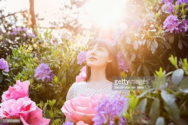 Woman standing in between giant flower bush.
