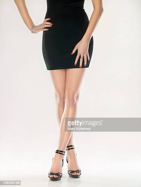 woman standing in black dress - beautiful legs in high heels stock-fotos und bilder