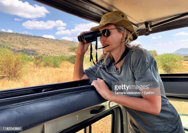 woman standing in car during safari - safari stock pictures, royalty-free photos & images