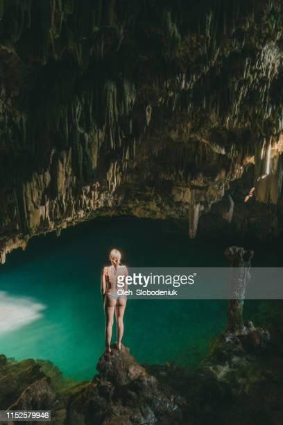 mujer de pie en la cueva de isla de flores - flores indonesia fotografías e imágenes de stock