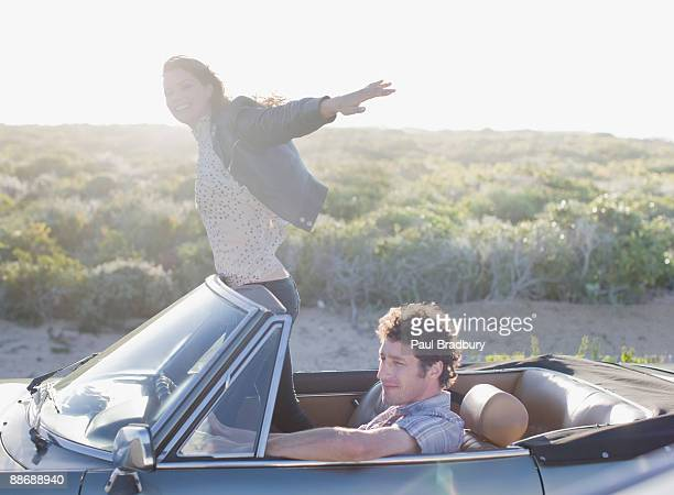 Woman standing in convertible