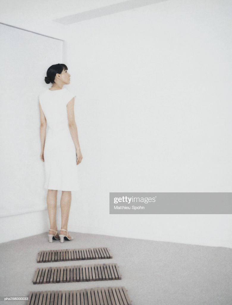 Woman standing in corner of room at end of path of wooden rectangles : Stockfoto