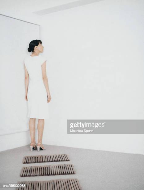 Woman standing in corner of room at end of path of wooden rectangles
