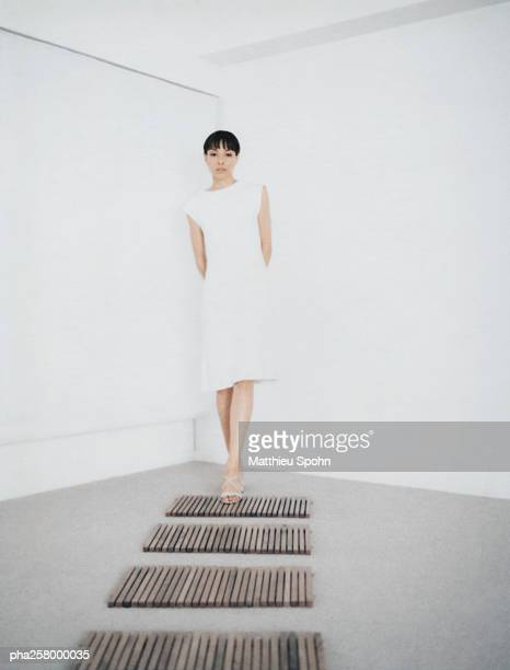 Woman standing in corner of room stepping on to path
