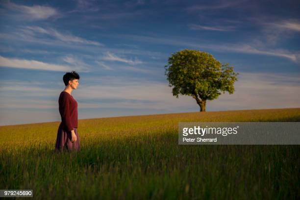 Woman Standing in Cornfield with one tree.