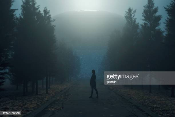 woman standing in country road against ufo - military invasion stock pictures, royalty-free photos & images