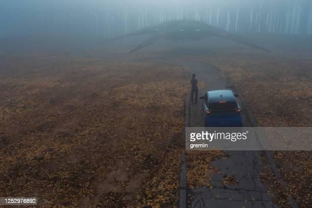 ufoに対する田舎道に立っている女性 - 誘拐事件 ストックフォトと画像