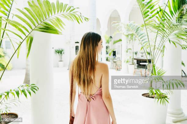woman standing in courtyard of luxury shopping boutique - dreiviertelansicht stock-fotos und bilder