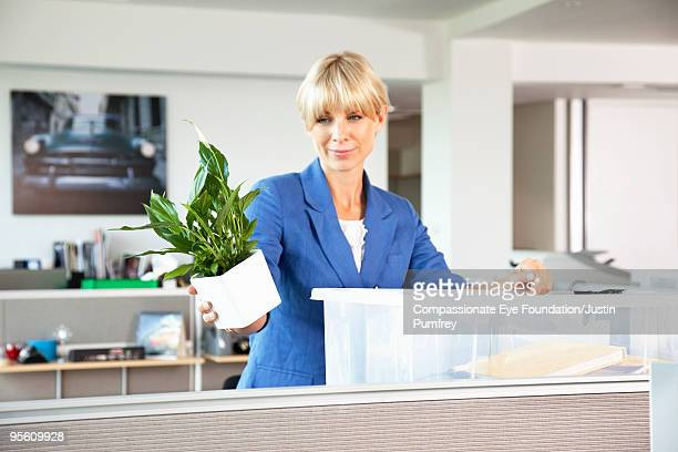 "woman standing in cubicle holding a potted plant - ""compassionate eye"" - fotografias e filmes do acervo"