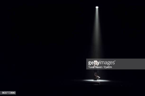 woman standing in darkroom - spotlit stock pictures, royalty-free photos & images