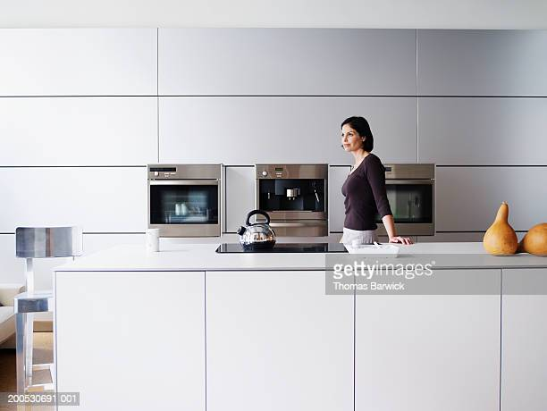 Woman standing in domestic kitchen, side view