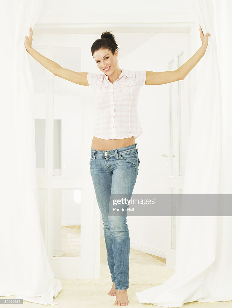Woman standing in doorway, arms outstretched : Stock Photo