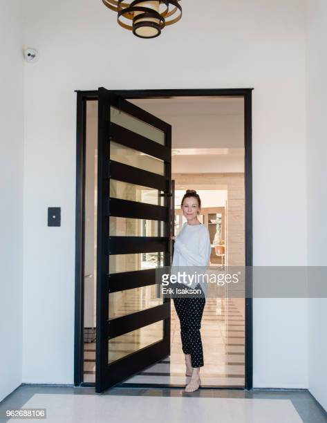 woman standing in doorway of house - doorway stock pictures, royalty-free photos & images