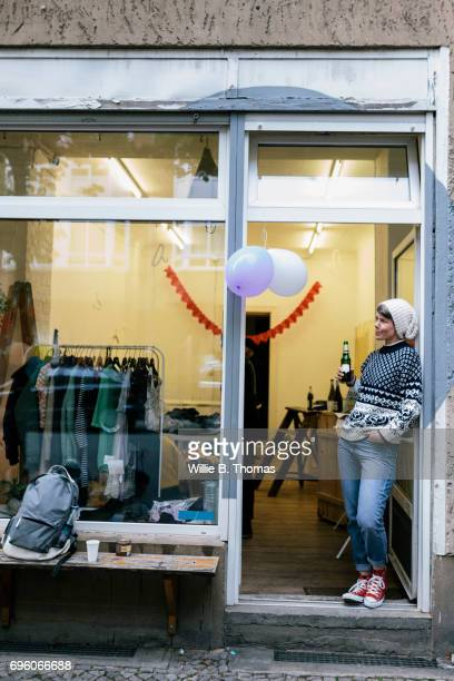 woman standing in doorway of newly opened vintage store - opening event stock photos and pictures