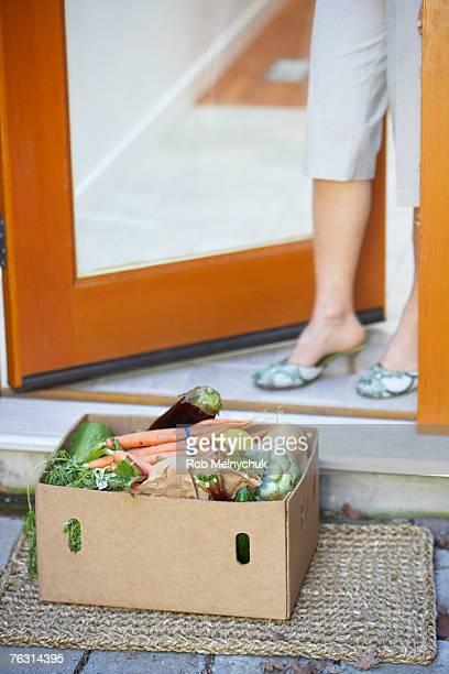 Woman standing in doorway with box of vegetables on doorstep
