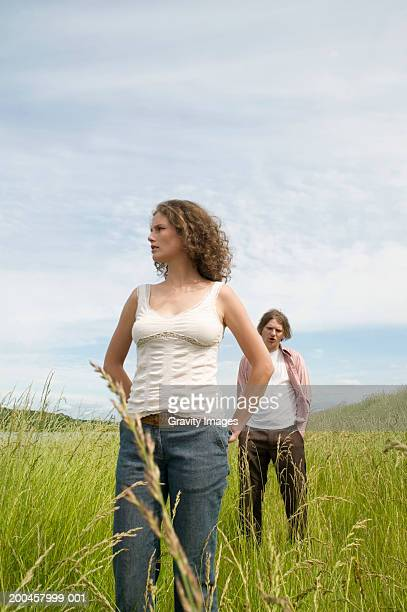 Woman standing in field with hands on hips, man standing in background