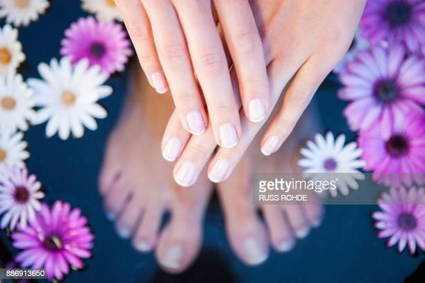 woman standing in foot bath, showing manicured hand, overhead view - womens beautiful feet stock pictures, royalty-free photos & images