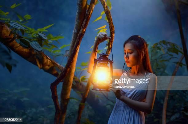 woman standing in forest holding a lantern, thailand - ランタン ストックフォトと画像
