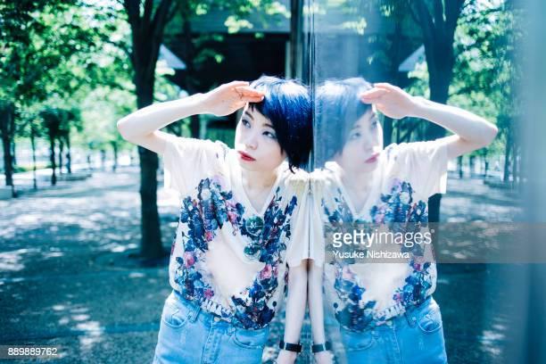 a woman standing in front of a mirror - yusuke nishizawa stock-fotos und bilder