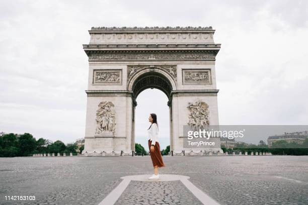 a woman standing in front of arc de triompheyoung in paris city. - パリ凱旋門 ストックフォトと画像