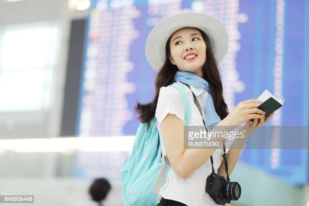 Woman Standing in Front of Arrivals and Departures Board