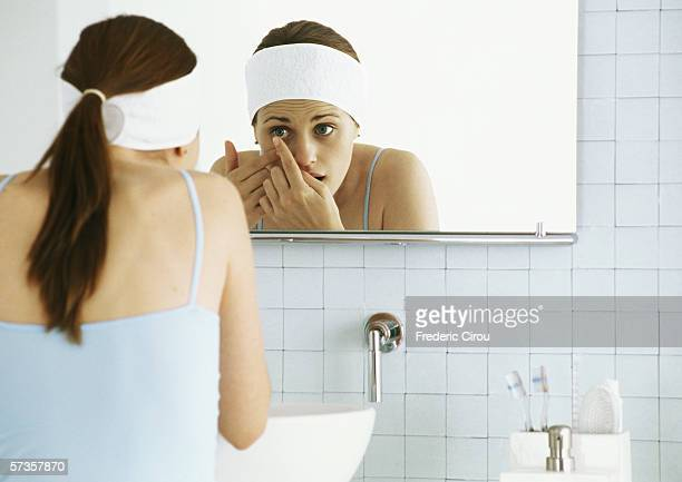 Woman standing in front of bathroom mirror, inserting contact lens