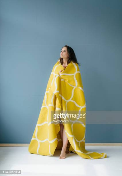 woman standing in front of blue wall, wrapped in yellow rug - bettwäsche stock-fotos und bilder