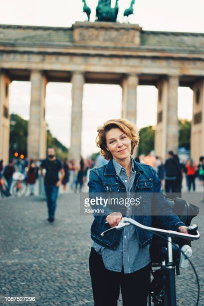 woman standing in front of brandenburg gate in berlin, germany - mid adult stock pictures, royalty-free photos & images