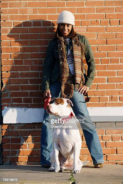Woman standing in front of brick wall with pitbull terrier