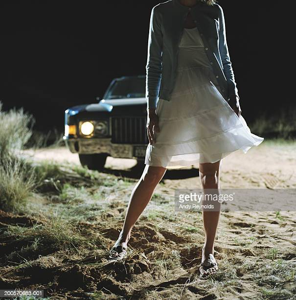 Woman standing in front of car in desert at night, low section