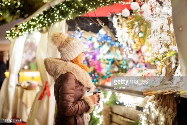 frau steht vor weihnachtsmarktstand - one night stand stock-fotos und bilder