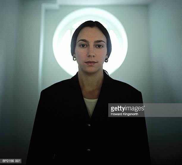 woman standing in front of door with circular window, portrait - angel halo stock pictures, royalty-free photos & images